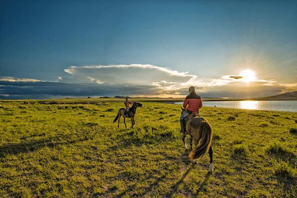 モンゴルの大草原で馬に乗る人