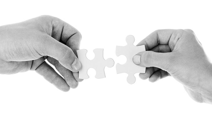 パズルを合わせるふたつの手