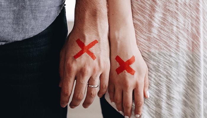 ×印のついた男女の手